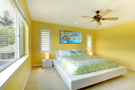 apartment: Yellow bright bedroom with green bedding and white bed.
