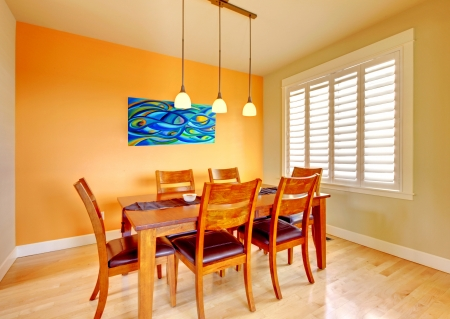 dining table and chairs: Orange dining room with wood table and hardwood floor.