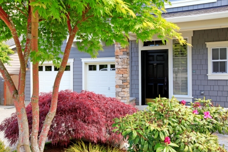 Linda nova casa grande com duas portas de garagem e porta da frente preto.