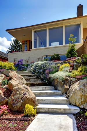 One story modern house exterior with staircase and flowers.