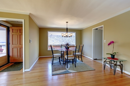 molding: Dining room with flont door and hardwood floor and round glass table Stock Photo