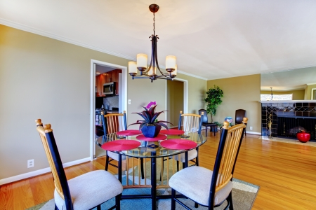 Dining room with round table and fireplace in green and pink. photo