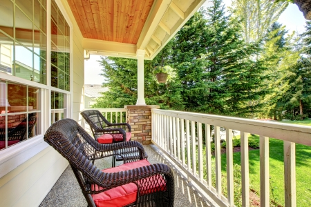 front exterior: Front covered porch with brown chairs and red cushions. Stock Photo