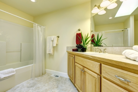 Simple large bathroom with tub and wood cabinets wih beige floor. photo