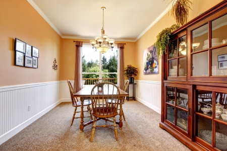 Peach color dining room with beige carpet and simpel furniture. photo