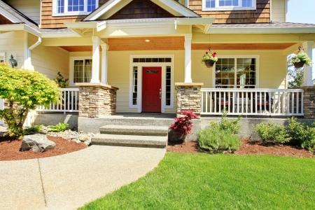 fachada de casa: El porche delantero de la casa americana con puerta roja.