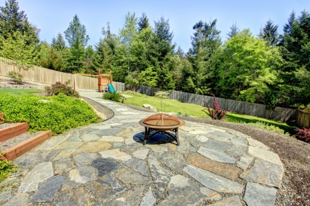 fenced: Large fenced backyard with stone and fire pit with trees. Stock Photo