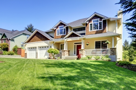 summer house: Large American beautiful house with red door and two white garage doors. Stock Photo