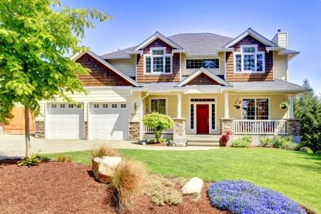 레드 도어와 두 개의 흰색 차고 문이있는 대형 미국의 아름다운 집.