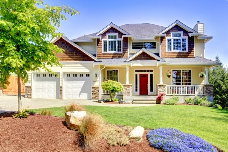 Gran casa americana hermosa con la puerta roja y dos puertas de garaje blancos.