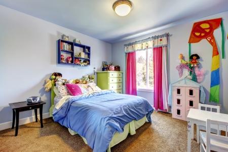 clean home: Blauwe slaapkamer van de baby meisje met speelgoed en een groot bed. Stockfoto