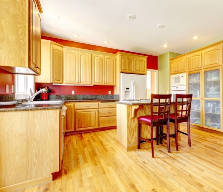 Yellow kitchen with island and yellow wood with red and green colors. photo