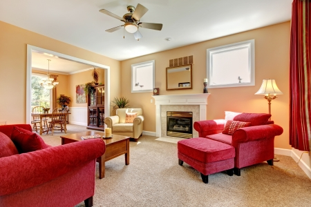 room: Beautiful peach and red liiving room interior with firepalce and red furniture. Stock Photo