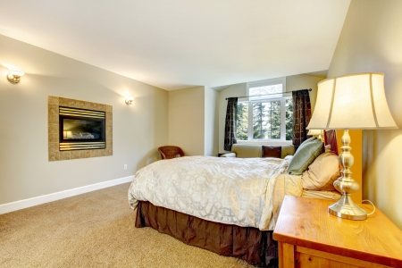 nightstand: Large bedroom with fireplace and nightstand with lamp and brown carpet.