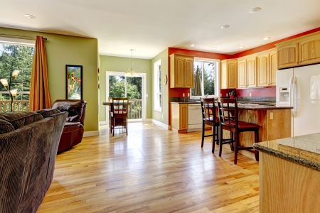 wood floor: Kitchen with yellow wood floor and green wall near living room.