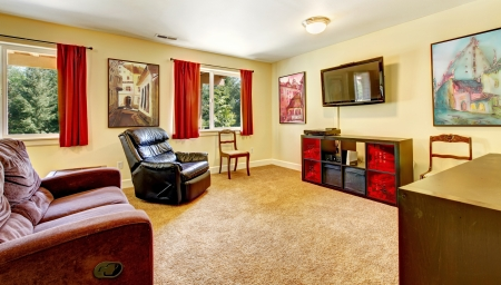 Tv living room with art and red curtains and beige carpet with brown furniture.