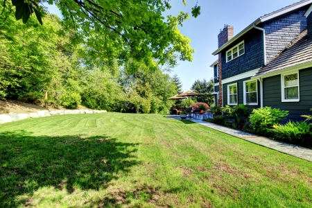 Blue large house with backyard and green landscape with trees. Stock Photo - 14615313