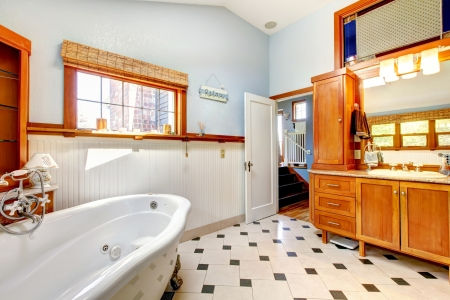 Large classic blue bathroom interior with tub and tiles and wood cabinets. Stock Photo - 14615036