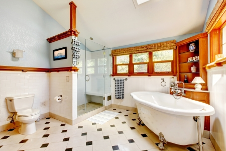 Large classic blue bathroom interior with tub and tiles and wood cabinets. photo