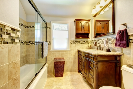 Classic bathroom with natural stone tiles and wood cabinet. photo