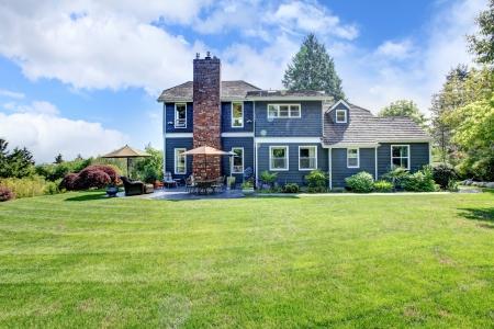 Grote blauwe huis exterieur met gras en schoorsteen.