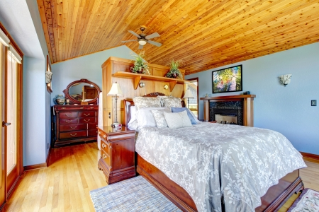 Beautiful blue bedroom with wood ceiling and fireplace. photo