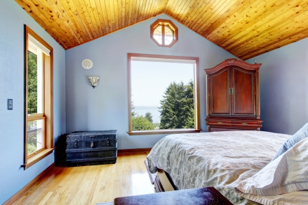 Blue bedroom with wood ceiling and bed, large windows interior photo