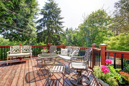 lawn area: Open large deck with chairs and table home exterior with trees on the back. Stock Photo