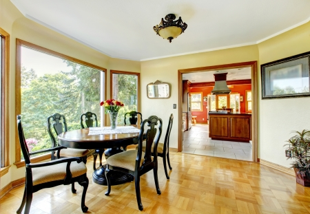 dining table and chairs: Dining room with large windows and hardwood floor.