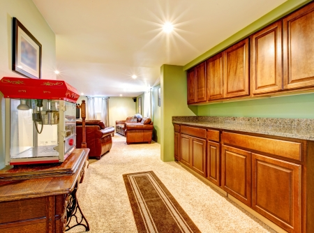 Basement interior with cabinets, green walls and popcorn machine. photo