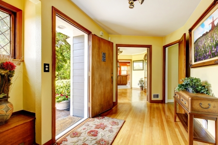 Large old luxury house entrance interior with art and yellow walls.