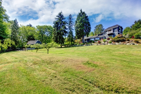 Large property with blue house and trees with blue sky. Stock Photo - 14615299