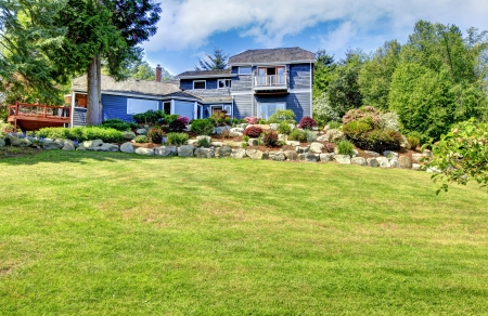 Large blue house exterior with green hill and stone walls. photo