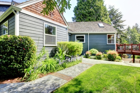 Grey house side exterior with deck and green landscape. Stock Photo - 14615294