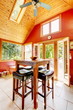 Luxury vaulted wood ceiling dining room with red walls and tile floor. photo
