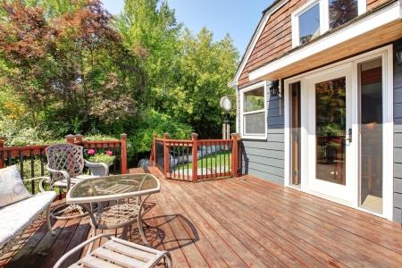 Huis exterieur met grote open dek en tuinmeubilair.