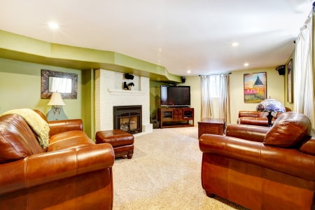 Tv room with green walls, leather sofas and fireplace and beige carpet. photo