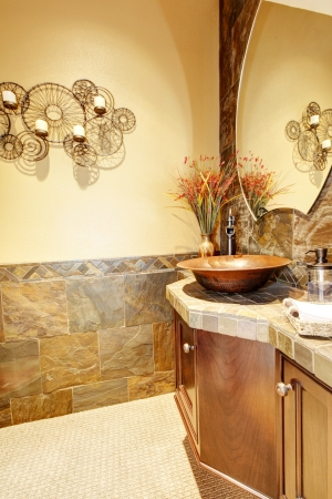 Sink with wood cabinet and stone tiles in the small bathroom. Stock Photo - 14615159