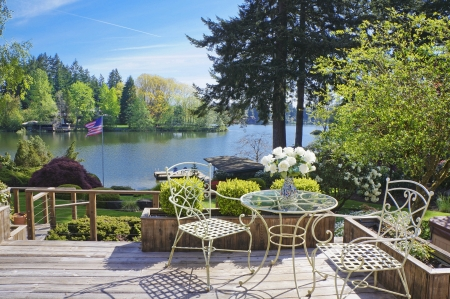 lake house: Deck with chairs and table with lake view and spring landscape.