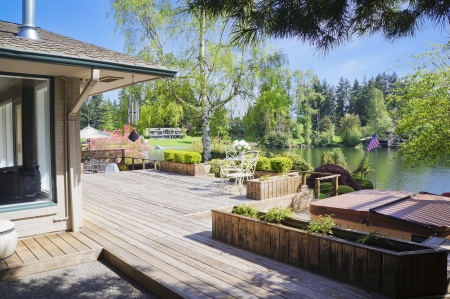 Spring large deck and house view with lake and tub