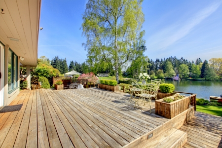 wood deck: Large wood deck near house with lake and spring landscape.