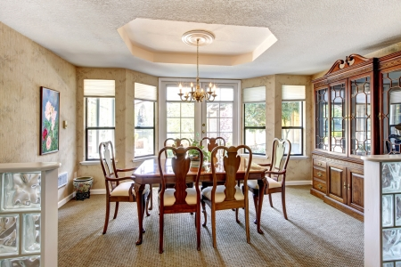 Elegant dining room interior with brown table and chairs.