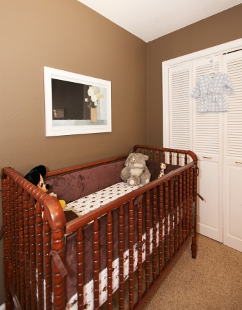 Cherry wood baby crib in nursery interior with brown wall.