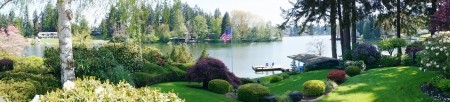 Back yard landscape with spring blooming flowers and lake and American flag. photo