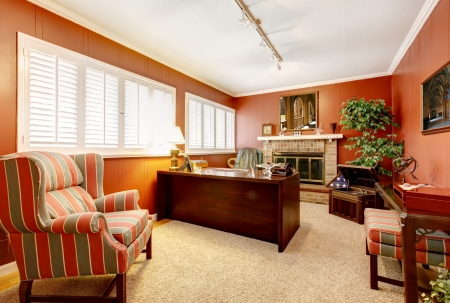 residential homes: Home office interior with red walls and fireplace and classic furniture.