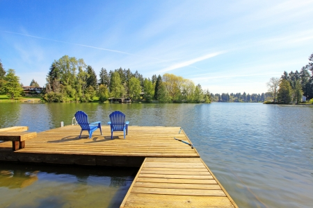 lake house: Lake spring waterfront with pier and two blue chairs.