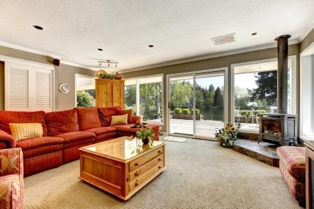 sala de estar: Sala de estar con muchas ventanas, un sof� rojo y una estufa.
