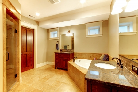 bathroom mirror: Beautiful large bathroom with two sinks and tub.