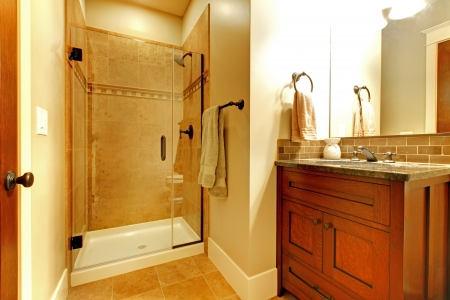 Bathroom with wood cabinet and tile shower with golden tone.