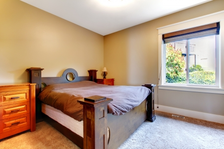 nightstand: Simple classic new bedrom with nice bed and dresser with beige walls.